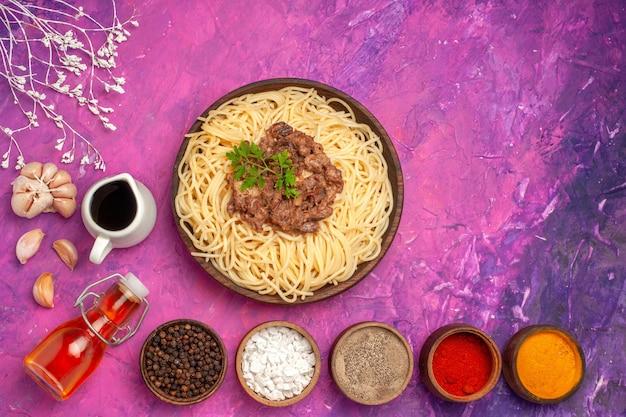 Vue de dessus des spaghettis cuits avec de la viande hachée sur un plat de pâtes à la pâte d'assaisonnement de table rose