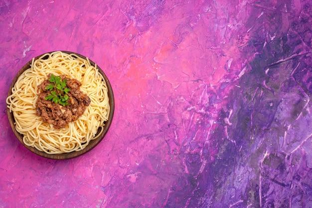 Vue de dessus des spaghettis cuits avec de la viande hachée sur le plat de pâtes de repas de pâte de table rose