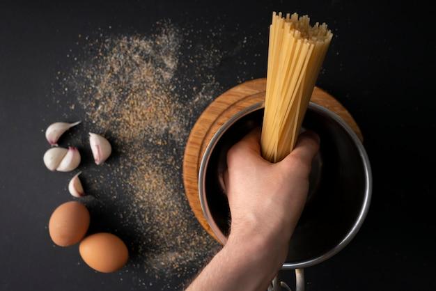 Vue de dessus de spaghettis durs crus dans une casserole en métal, eau bouillante, ingrédients pour cuisiner