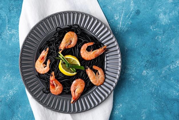 Vue de dessus des spaghettis à l'encre de seiche avec des crevettes et des tranches de citron sur plaque grise sur fond bleu avec espace de copie