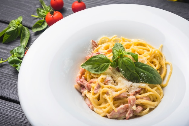 Une vue de dessus de spaghettis avec des feuilles de basilic et des garnitures au fromage sur une plaque blanche