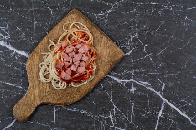 Vue de dessus de spaghettis de pâtes maison et saucisses avec sauce.
