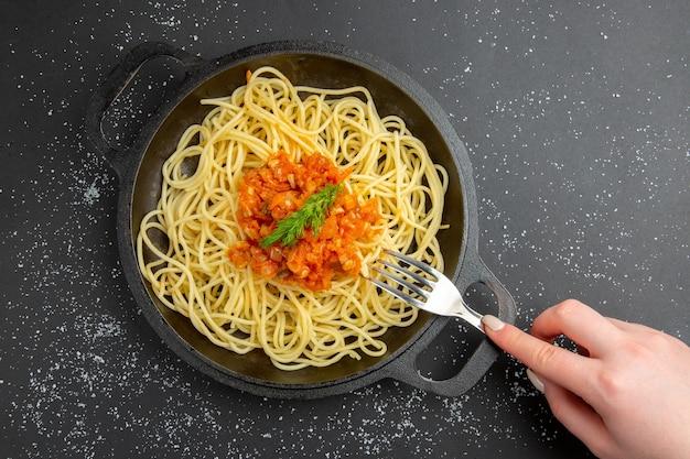 Vue de dessus des spaghettis avec sauce dans une fourchette de poêle à frire dans une main féminine sur un espace libre de table noire