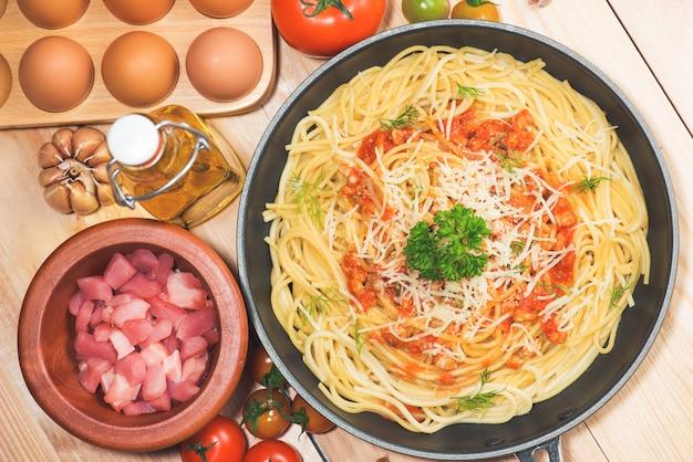 Vue de dessus des spaghettis à la sauce tomate et de la viande sur une table en bois.