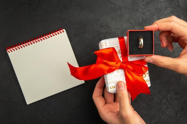 Vue de dessus en spirale bloc-notes cadeau bague de fiançailles dans la boîte dans les mains des femmes sur fond sombre