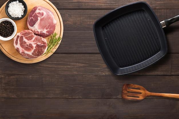 Vue de dessus steak de côtelette de porc cru, poêle à griller et spatule sur le fond en bois. copyspace pour votre texte