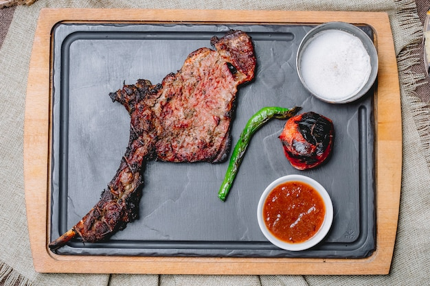 Vue de dessus steak grillé avec légumes grillés avec ketchup et mayonnaise
