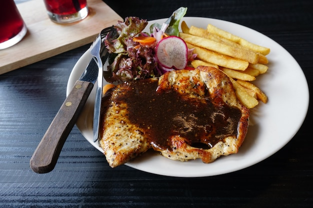 Vue de dessus de steak de viande de poulet sur une table en bois noire avec frites et légumes français