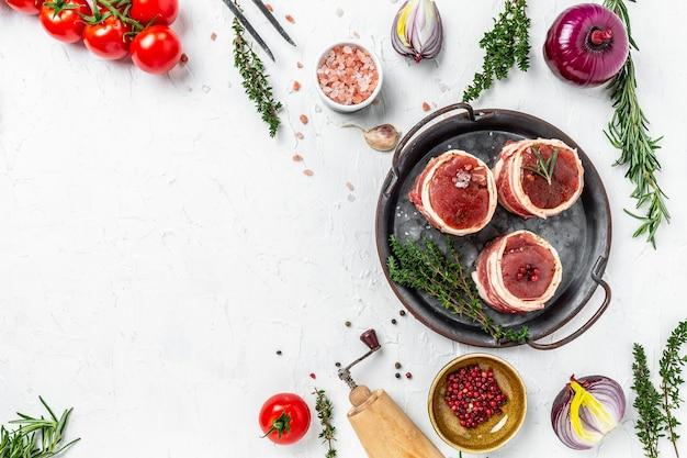 Vue de dessus des steaks de filet de bœuf enveloppés de bacon servis sur un vieux plateau de viande sur fond clair, vue de dessus.