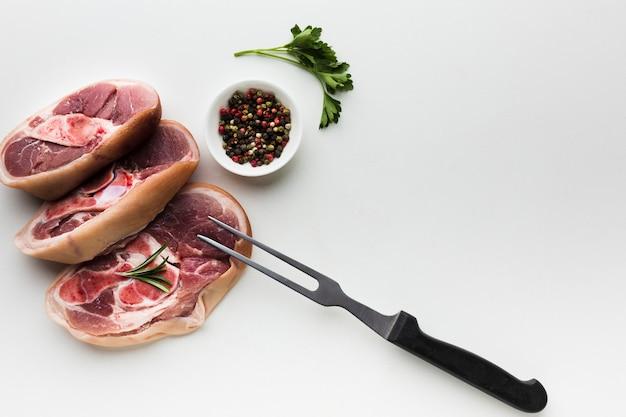 Vue de dessus des steaks frais avec du poivre sur la table