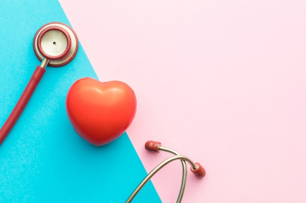 Vue de dessus stéthoscope rouge et forme de coeur rouge sur rose et bleu
