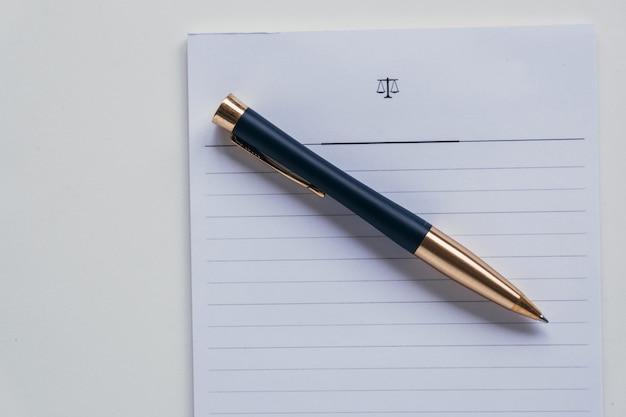 Vue de dessus d'un stylo roller placé sur un morceau de papier rayé blanc