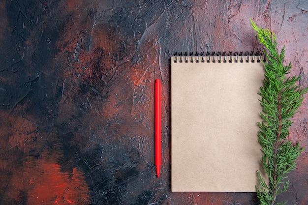 Vue de dessus stylo rouge un bloc-notes avec petit arc une branche de pin sur une surface rouge foncé avec place de copie