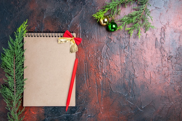 Vue de dessus stylo rouge sur un cahier de branches d'arbres de pin boule d'arbre de noël sur l'espace libre de surface rouge foncé