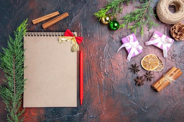 Vue de dessus stylo rouge un cahier branches d'arbres de pin boules d'arbres de noël fil de paille cannelle anis étoilé cadeaux de noël sur une surface rouge foncé