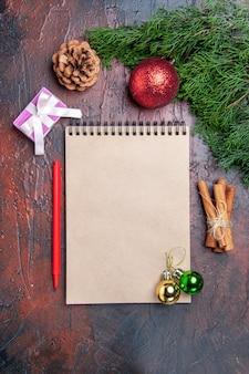 Vue de dessus stylo rouge un cahier branches d'arbres de pin jouets de boule d'arbre de noël bâtons de cannelle sur la photo de noël de surface rouge foncé