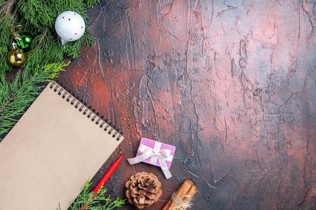 Vue de dessus stylo rouge un cahier branches d'arbres de pin jouets de boule d'arbre de noël sur l'espace libre de surface rouge foncé