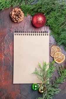Vue de dessus stylo rouge un cahier branches d'arbres de pin jouets de boule d'arbre de noël sur une surface rouge foncé
