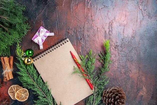 Vue de dessus stylo rouge sur un ordinateur portable branches de pin tranches de citron séchées bâtons de cannelle sur l'espace libre de surface rouge foncé