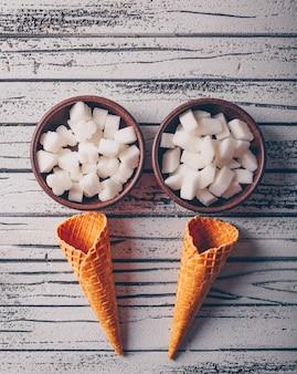 Vue de dessus de sucre blanc dans des bols avec une gaufre à la crème glacée