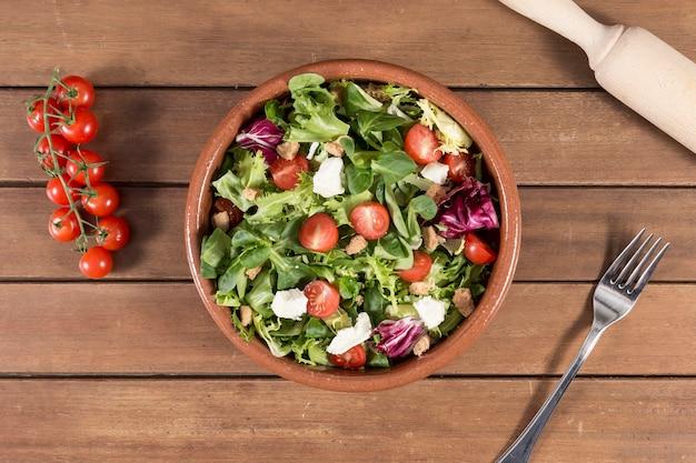 Vue de dessus de la surface en bois avec une salade délicieuse