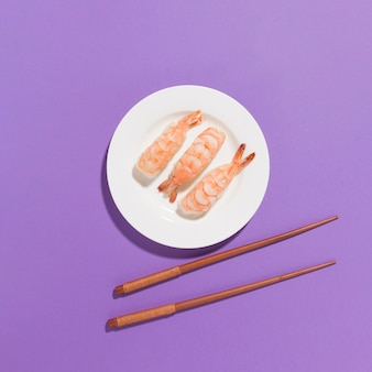 Vue de dessus des sushis frais avec des baguettes sur la table