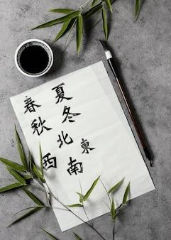 Vue de dessus des symboles chinois écrits avec de l'encre sur du papier blanc
