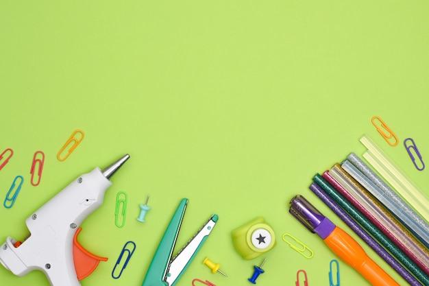 Vue de dessus de table artisanale. outils et articles de papeterie pour la créativité. pistolet à colle, colle à paillettes, punch créatif, trombones, marqueur et ciseaux bouclés sur fond vert avec espace de copie.