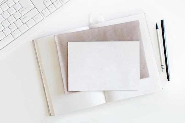 Vue de dessus sur une table blanche avec clavier, cahier avec des pages blanches, enveloppe d'artisanat, carte postale claire et un stylo avec un crayon. lay plat.