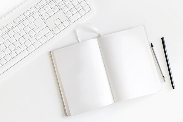 Vue de dessus sur une table blanche avec clavier, cahier avec des pages blanches et un stylo avec un crayon. lay plat.