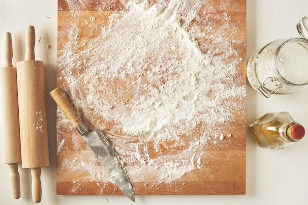 Vue de dessus sur table blanche avec planche de bois isolée avec couteau, deux rouleaux à pâtisserie, bouteille d'huile d'olive, pot transparent avec de la farine. processus de cuisson de présentation