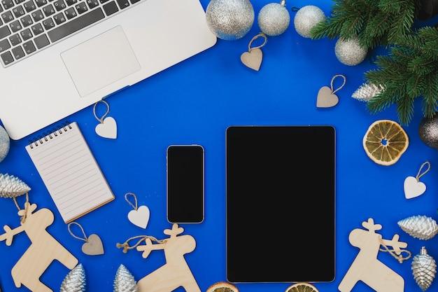 Vue de dessus d'une table bleue avec un ordinateur portable et un décor de noël