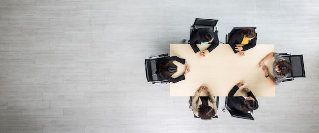 Vue de dessus de la table en bois de conférence de réunion avec six femmes d'affaires exécutives assises sur chaque chaise discutant et parlant d'affaires en travail d'équipe dans la salle de réunion.