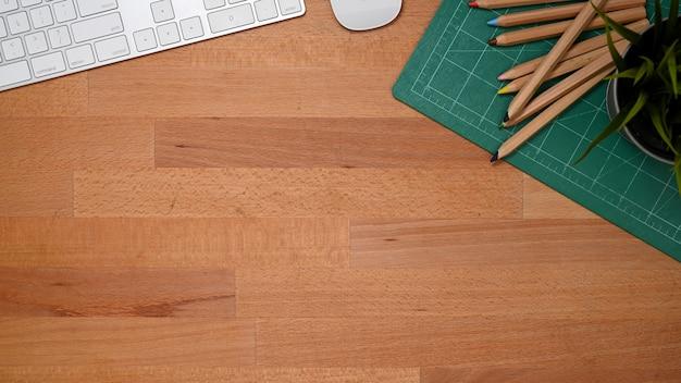 Vue de dessus de la table en bois avec espace copie, crayons de couleur, appareil informatique dans la salle de bureau à domicile