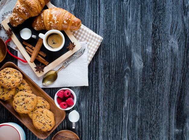 Vue de dessus d'une table en bois pleine de gâteaux, fruits, café, biscuits, épices et plus