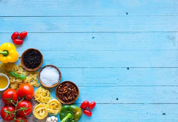 Vue de dessus d'une table en bois pleine d'ingrédients de pâtes italiennes comme les poivrons, tomates, huile d'olive, base