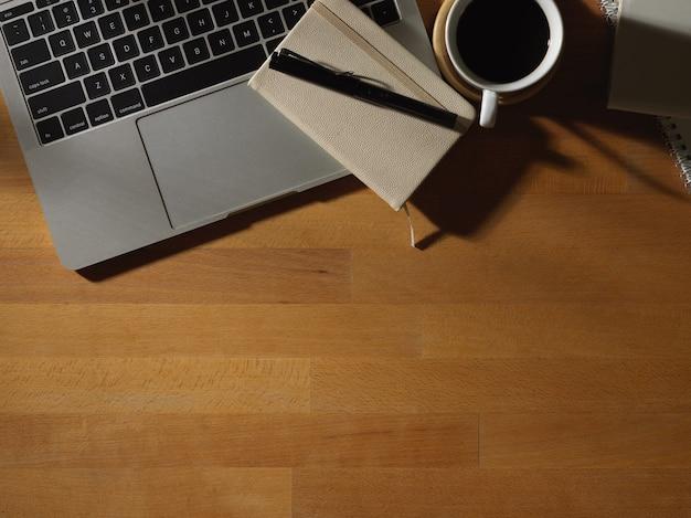 Vue de dessus de la table en bois avec tasse de café papeterie ordinateur portable