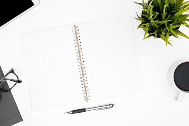 Vue de dessus de table de bureau blanc avec bloc-notes vierge avec lignes de la grille et des fournitures.