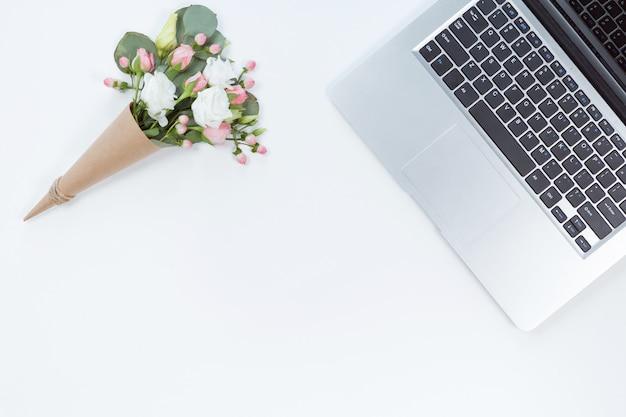 Vue de dessus de la table de bureau blanche avec ordinateur portable, ordinateur portable, composition de la fleur. espace de copie, pose à plat.