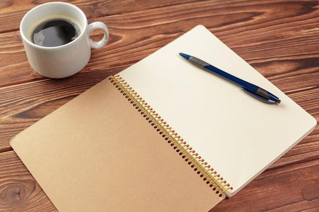 Vue de dessus de table de bureau de bureau, bloc-notes avec des pages blanches sur une table en bois