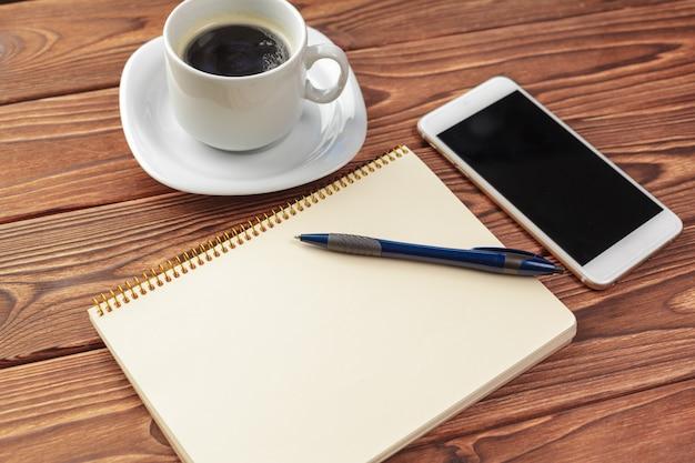 Vue de dessus de table de bureau de bureau. bloc-notes avec des pages blanches sur une table en bois