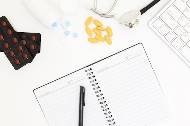 Vue de dessus de la table de bureau du médecin avec du papier blanc sur blanc
