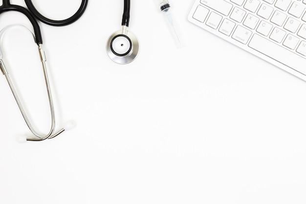 Vue de dessus de la table de bureau du médecin avec du papier vierge sur fond blanc,