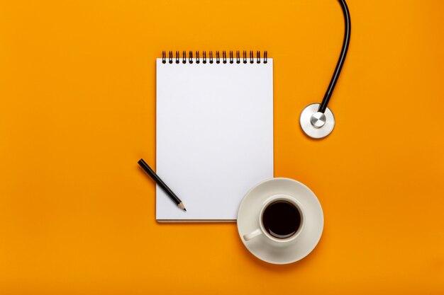 Vue de dessus de la table de bureau de médecin avec stéthoscope, café et papier vierge sur le presse-papiers avec stylo.
