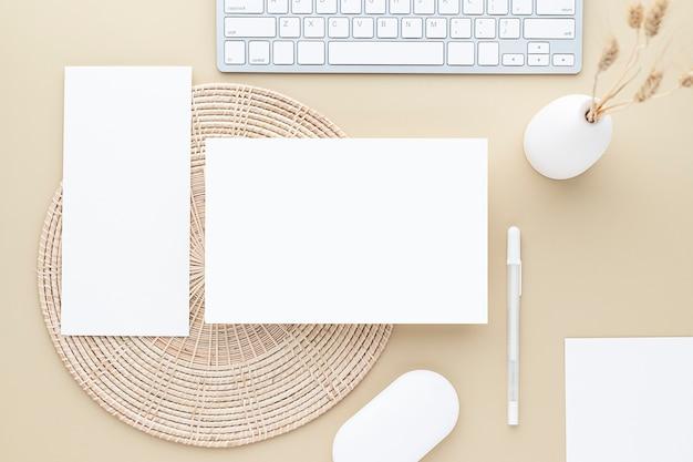 Vue de dessus de table de bureau. vase en céramique avec roseau et fournitures de bureau, table beige avec espace de copie, composition de lieu de travail de couleur beige, pose à plat