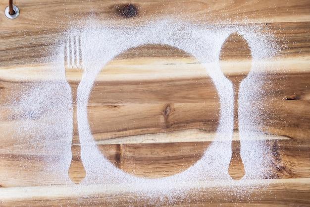 Vue de dessus de la table de cuisine avec assiette et couverts farine silhouette, fourchette et cuillère