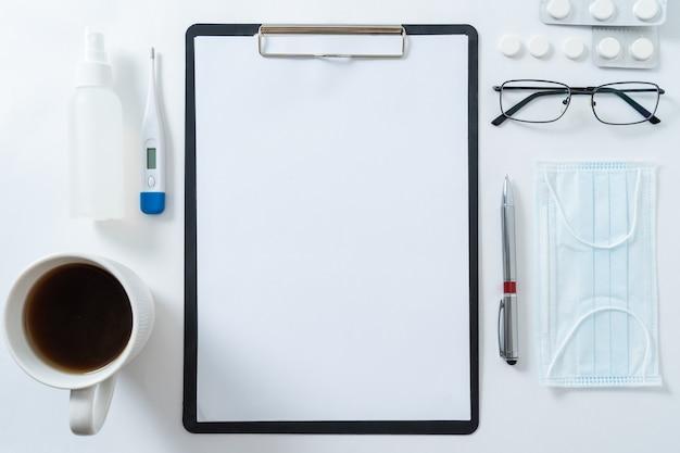 Vue de dessus de la table du bureau du médecin, papier vierge sur presse-papiers avec stylo. copiez l'espace.