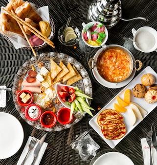 Vue de dessus de la table du petit-déjeuner avec des œufs confitures crêpes saucisses au fromage