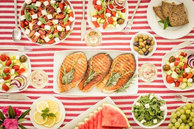 Vue de dessus de la table avec du poisson, des salades, des fruits et légumes