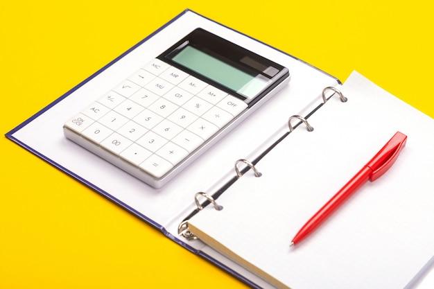 Vue de dessus de la table de l'espace de travail avec calculatrice, cahier et stylo isolé sur fond jaune